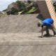 Man on roof performing a roof inspection for Frisco home